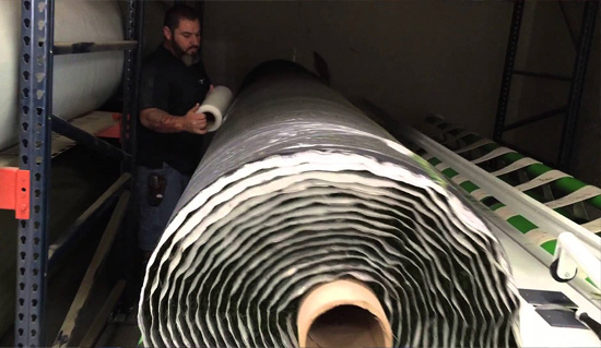Accu-Cut Machine wrapping large roll of artificial turf.
